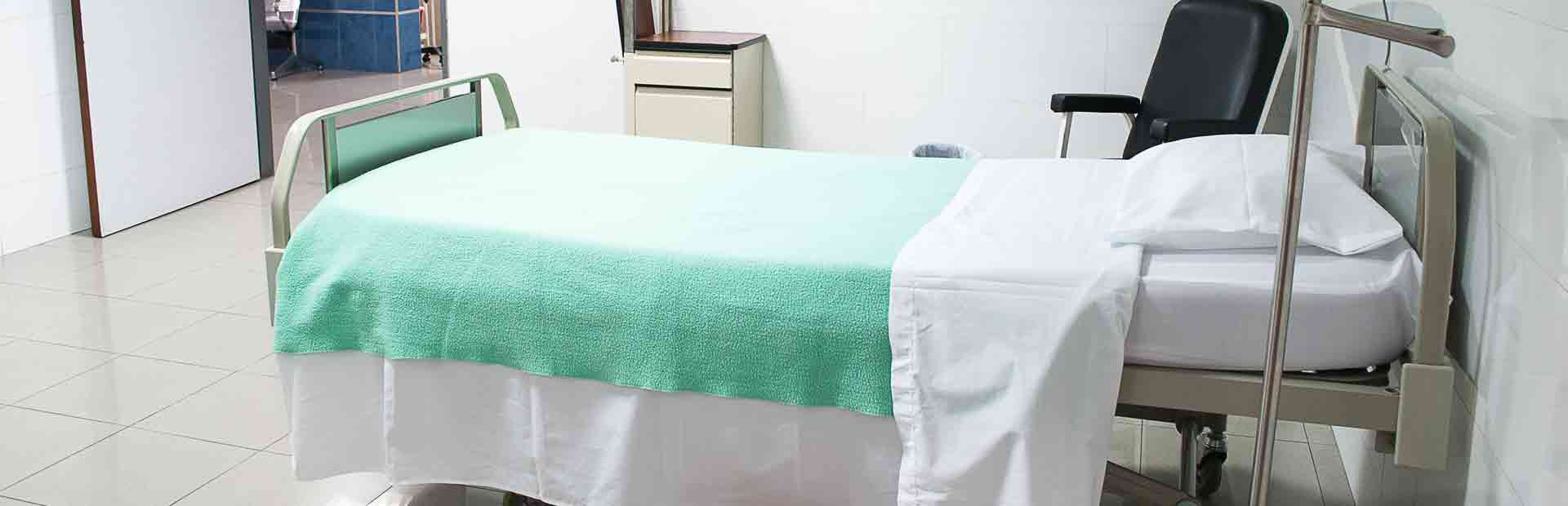 A hospital bed with a green blanket