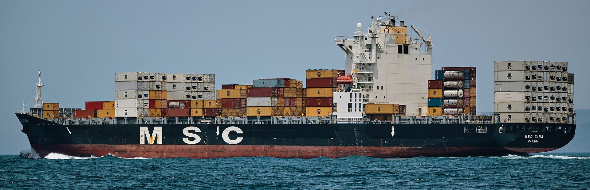 A cargo ship with many goods at sea